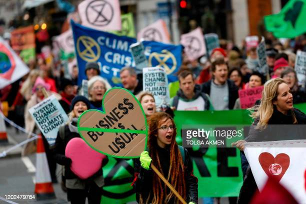 Climate activists hold up placards as they march during a protest organized by the climate change action group Extinction Rebellion in London on...