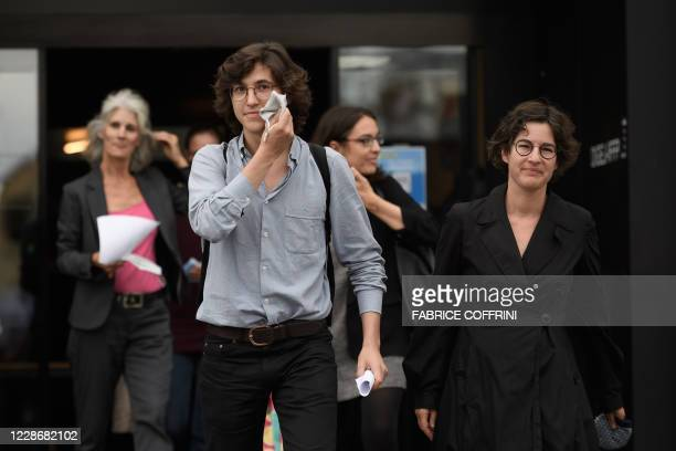 Climate activists Paul Castelain removes his protective face mask exiting the court on September 24 2020 in Renens near Lausanne after twelve Swiss...