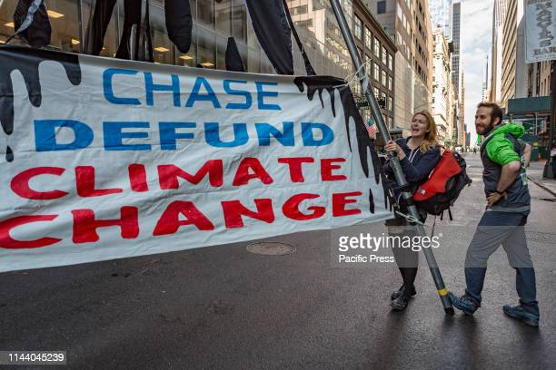 Climate activists protest Chase Bank's continued funding of the fossil fuel industry by setting up a tripodblockade in midtown Manhattan clogging...