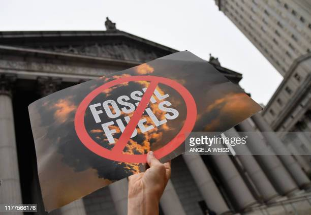 Climate activists protest on the fist day of the ExxonMobil trial outside the New York State Supreme Court building on October 22, 2019 in New York...
