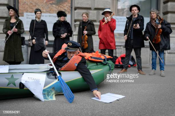 Climate activists re-enact a scene from the film Titanic during protest against Swiss bank Credit Suisse on February 13 in Zurich, as the group holds...