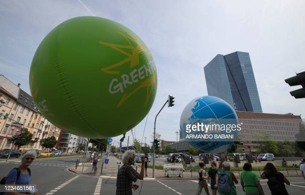 Climate activists walk with balloons featuring the Earth during a demonstration called by Fridays for Future, Greenpeace, KoalaKollektiv and others...