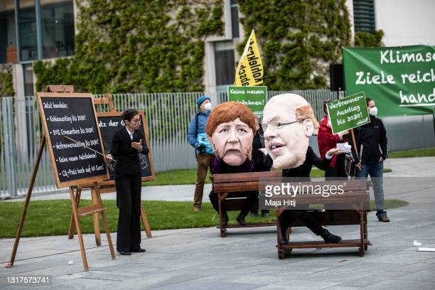 Climate activists wearing masks to look like German Chancellor Angela Merkel and Economy and Energy Minister Peter Altmaier gather in protest outside...