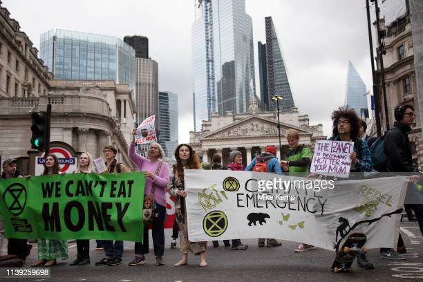 Climate change activist from the Extinction Rebellion group sings songs and block the streets outside the Bank of England in a swarming tactic in the...