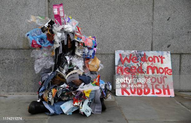 Climate change activist from the group Extinction Rebellion, dressed in plastic single-use packaging, demonstrates outside the Houses of Parliament...