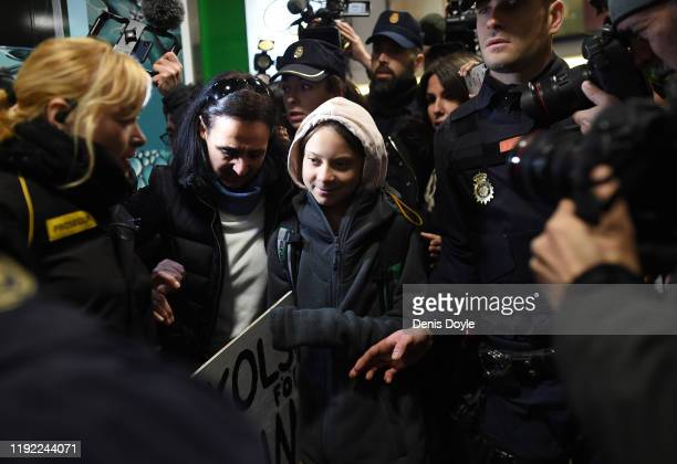 Climate change activist Greta Thunberg is escorted by police on her arrived at Chamartin train station in Madrid, on December 6, 2019. Greta is in...
