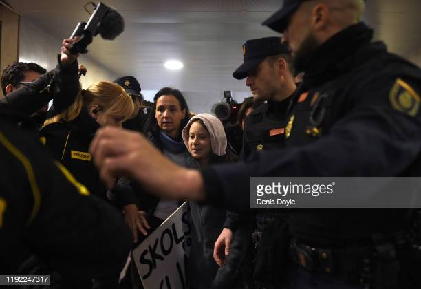 Climate change activist Greta Thunberg is escorted by police on her arrival at Chamartin train station in Madrid, on December 6, 2019. Greta is in...