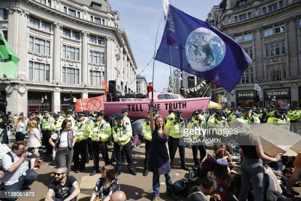 A climate change activist waves a flag as police officers keep watch during the ocupation of the road junction at Oxford Circus in central London on...