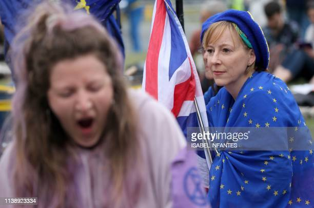 A climate change activist yawns as an antiBriexit demonstrator sits wrapped in an EU flag during the ongoing Brexit and Extinction Rebellion climate...