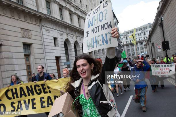 Climate change activists from the Extinction Rebellion group march up to block the street at Bank in the heart of the City of London financial...