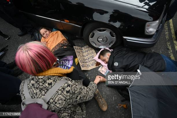Climate change activists from the group Extinction Rebellion lie on the road locked on to a hearse blocking the road in Trafalgar Square in central...