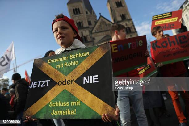 Climate change activists including a child carrying a sign with a Jamaican flag and urging the three German political parties of the socalled...