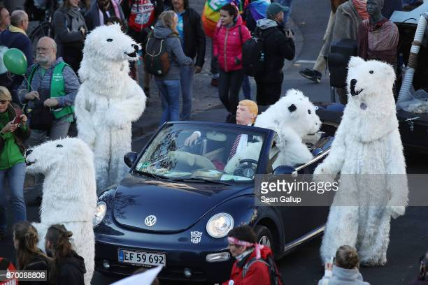 Climate change activists including one dressed as US President Donald Trump surrounded by polar bears march to demonstrate against coal energy and...