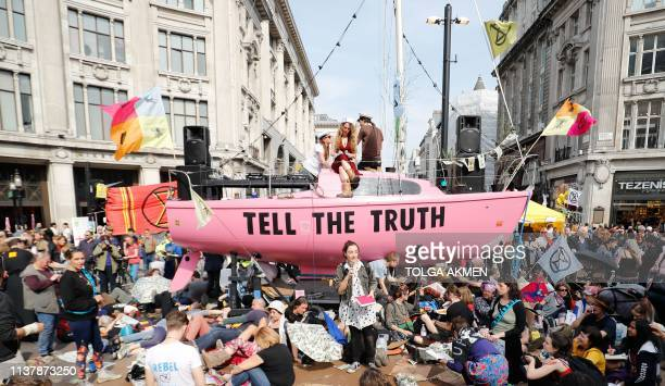 TOPSHOT Climate change activists listen to speeches at their encampment blocking the road junction at Oxford Circus in the busy shopping district in...