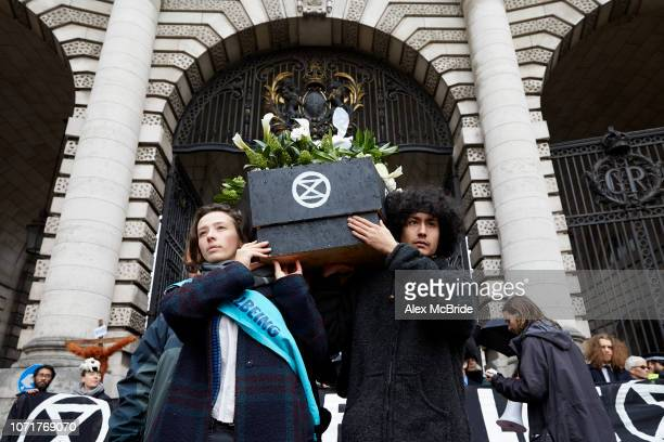 Climate change activists march a coffin symbolising the future of the planet if fossil fuel consumption continues towards Buckingham Palace during a...