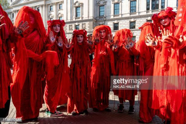 Climate change activists pose for photographs in Parliament Square in London on April 21 on the seventh day of an environmental protest by the...