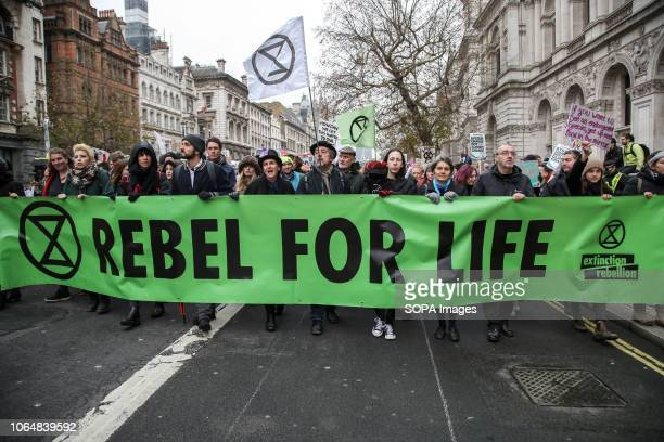 Climate change activists seen carrying a banner during the march Extinction Rebellion activists took part in a funeral march from Parliament Square...