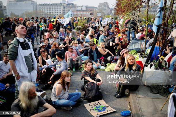 Climate change activists sit on Waterloo Bridge on the third day of its blockade by environmental protest group Extinction Rebellion in London on...