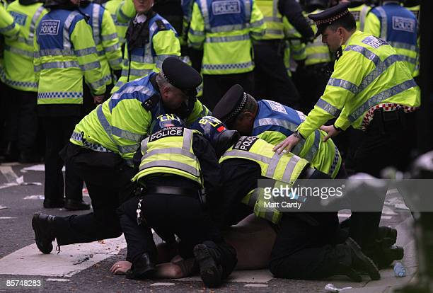 A climate change and anticapitalist activist is detained by police during a demonstration outside a branch of the Royal Bank of Scotland on April 1...