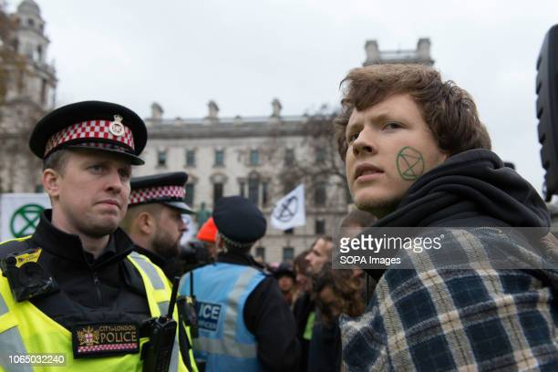 Climate change demonstrator seen with the Extinction Rebellion logo painted on his cheek Thousands of demonstrators from the new Extinction Rebellion...