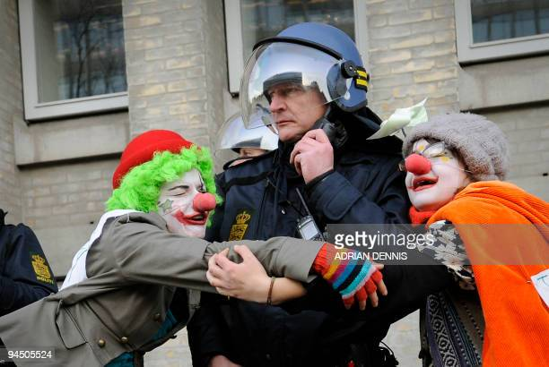 Climate change demonstrators dressed as clowns hug a police officer outside the Danish Foreign Ministry while demonstrators pass during the climate...