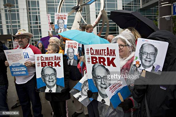 Climate change demonstrators hold signs in the likeness of Warren Buffett chairman and chief executive officer of Berkshire Hathaway Inc while...