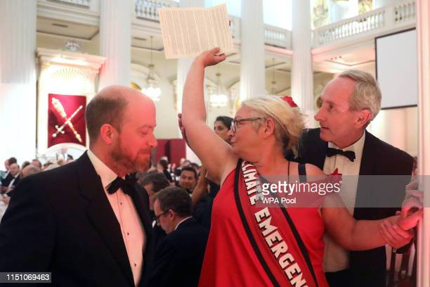 A climate change protester holding a letter is escorted out after interrupting a speech during the annual Mansion House dinner on June 20 in London...