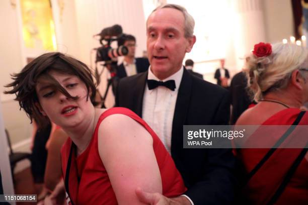 A climate change protester is escorted out after interrupting a speech during the annual Mansion House dinner on June 20 in London England Greenpeace...