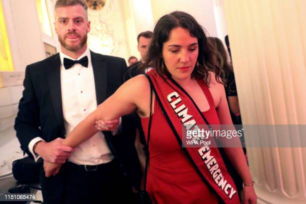 Climate change protester is escorted out after interrupting British Chancellor of the Exchequer Philip Hammond's speech during the annual Mansion...