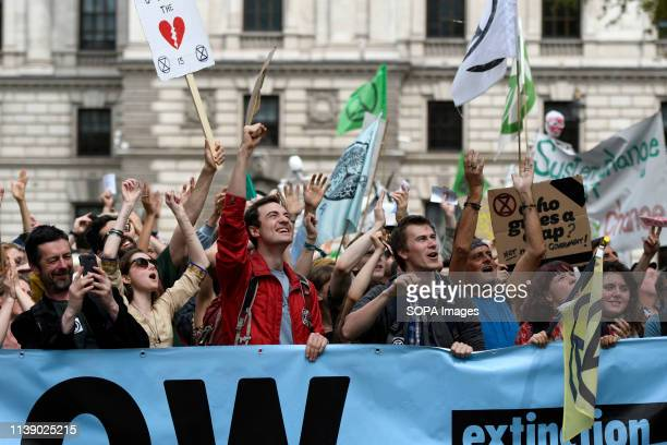 Climate Change protesters are seen behind a large banner shouting slogans during the Extinction Rebellion march in London Extinction Rebellion...