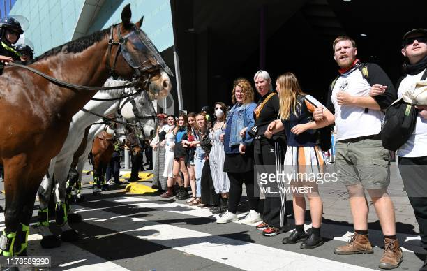 Climate change protesters attempting to blockade link arms in front of ploice horses at the International Mining and Resources Conference being held...