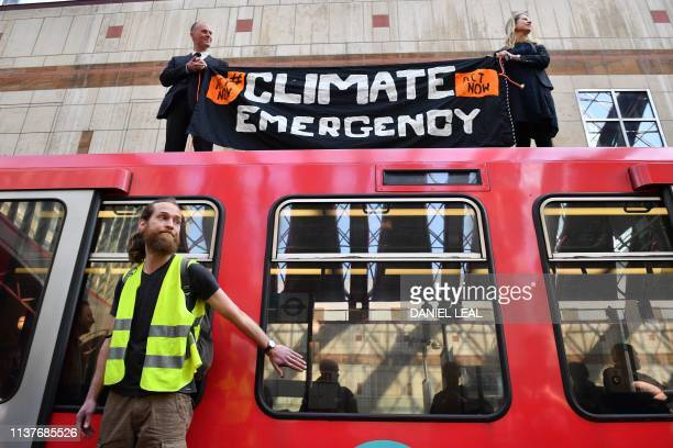 Climate change protestors one of whom has glued his hand to a window and two others who climbed atop a DLR train at Canary wharf station on the third...