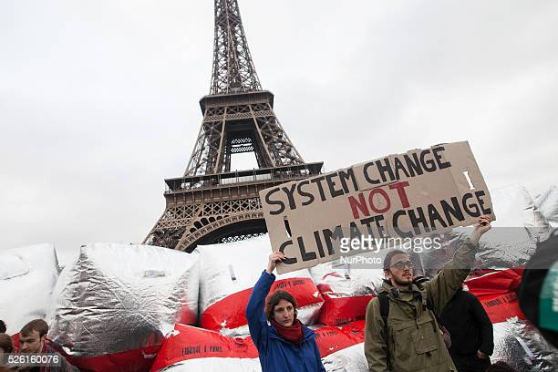 Climate demonstrators hold up a sign with the text quotsystem change not climate changequot on the bridge Pont D'i��na in front of the Eiffel Tower...