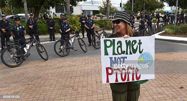 A climate protester holds up a placard at the G20 Finance Ministers and Central Bank Governors Meeting in Cairns on September 21 2014 Finance...