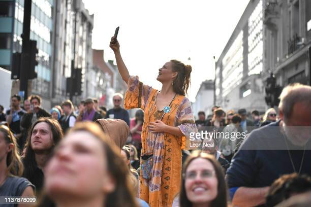 Climate protester takes a photo on a mobile phone at Oxford Circus during the fourth day of a coordinated protest by the Extinction Rebellion group...