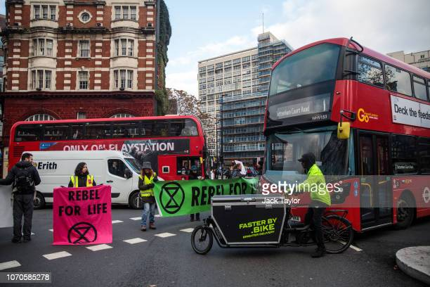 Climate protesters from the Extinction Rebellion group hold placards and banners as they block traffic in Elephant and Castle on November 21 2018 in...