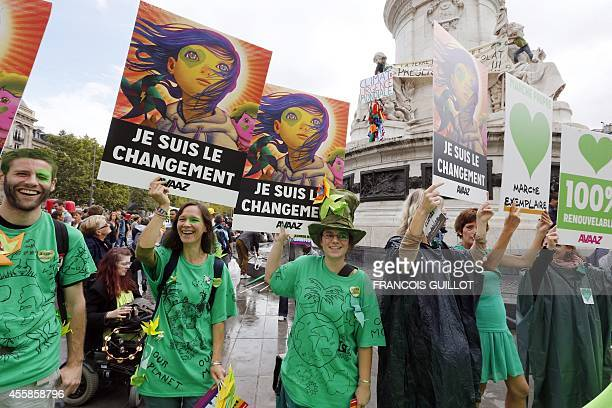 Climate protesters hold a banner reading ' I am the change' on the Republique's square during a demonstration to fight climate change on September 21...