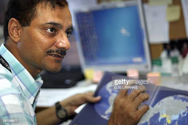 """Climate-warming-agriculture-rice,FEATURE"""" BY Cecil Morella This picture taken 17 July 2007 shows Indian plant geneticist Kumar Singh holding a world..."""
