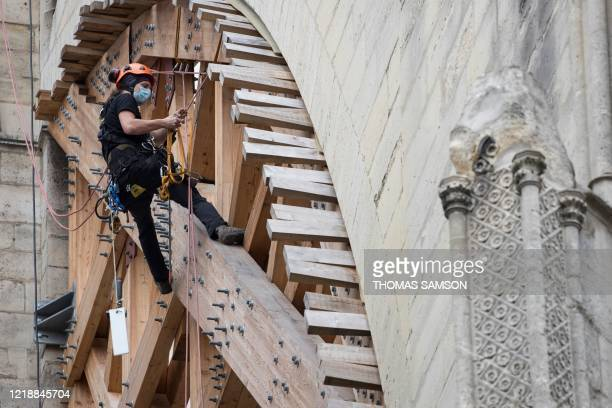 Climb worker works on a wooden consolidation of a flying buttress at the Notre-Dame cathedral after it was partially damaged in the April 2019 blaze,...