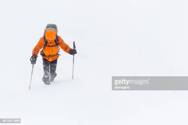 Climber approaching the summit of the mountain during snow storm
