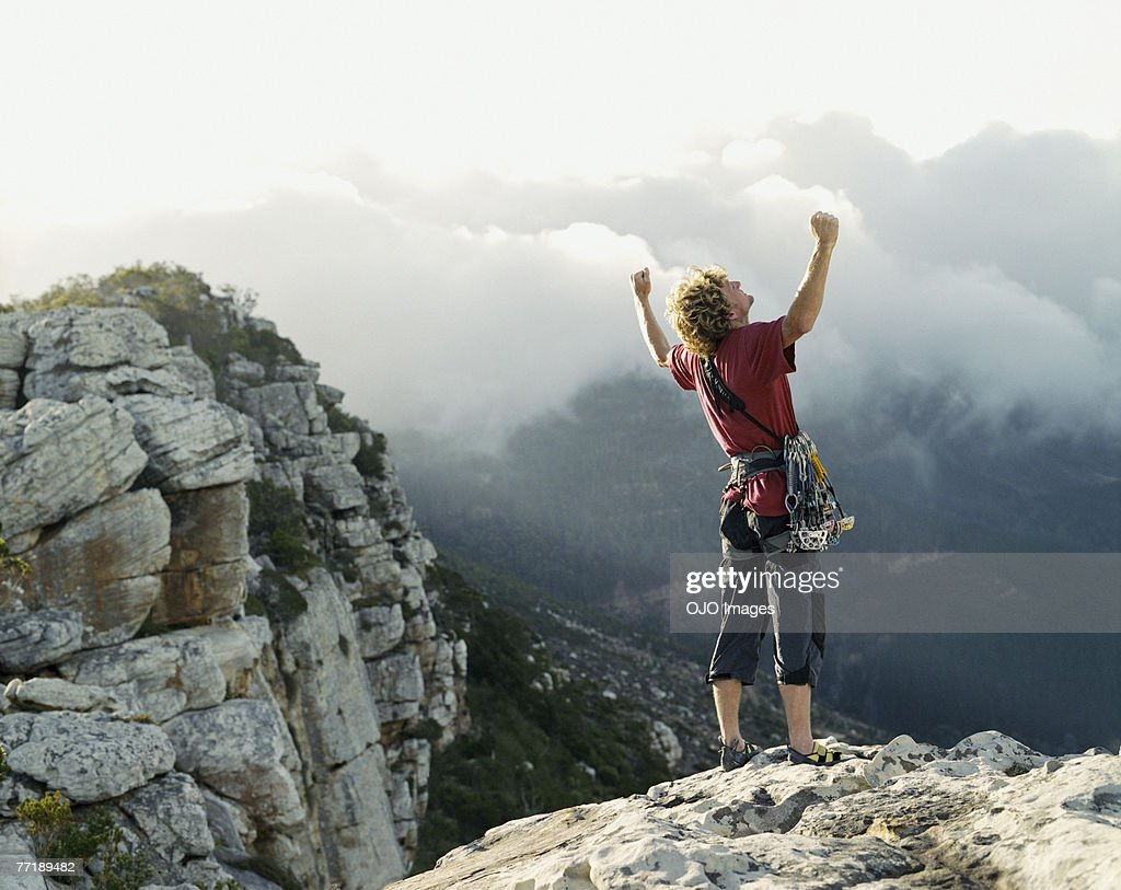 A climber at the top of the mountain victorious : Stock Photo