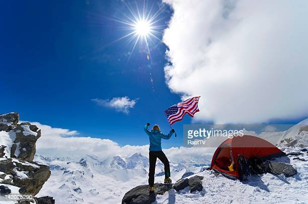 Climber celebrates on top of snowy mountain