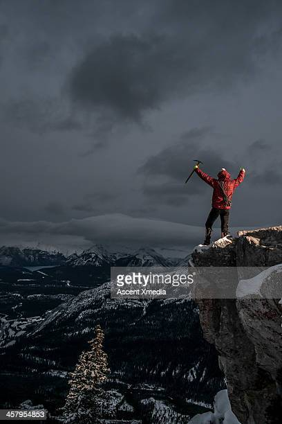 Climber celebrates with arms out, mountain summit