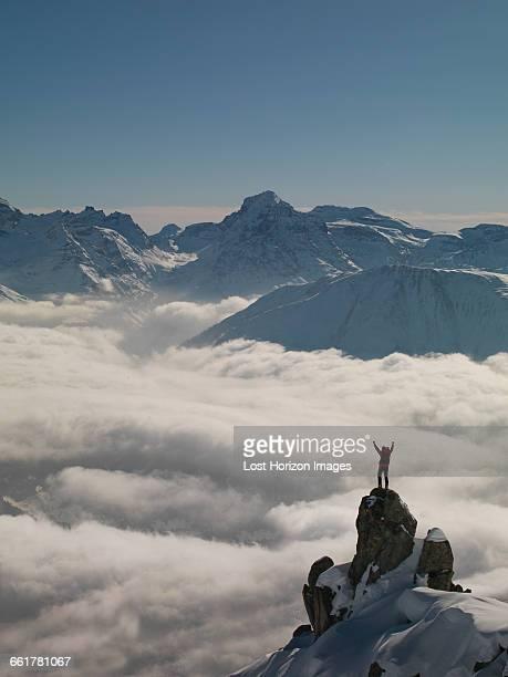 Climber celebrating on peak emerging from fog, Bettmeralp, Valais, Switzerland