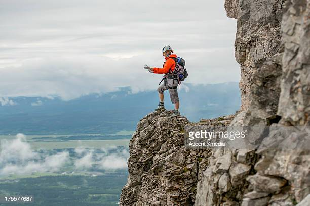 Climber checks map, on rock crest above valley