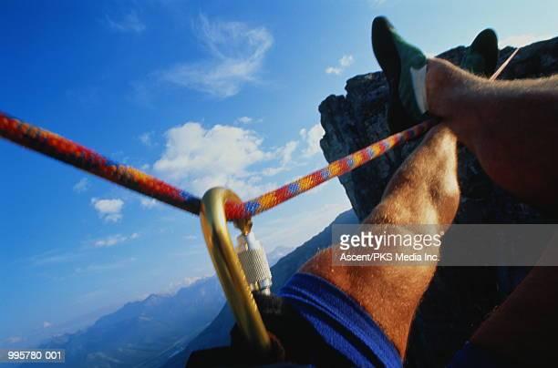 Climber during tyrolean traverse between rocks, close-up