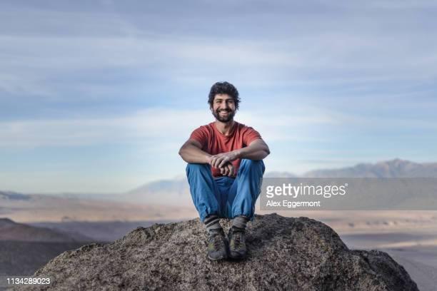 climber enjoying view on mountain peak, sierra nevada, bishop, california, usa - sitting stock pictures, royalty-free photos & images
