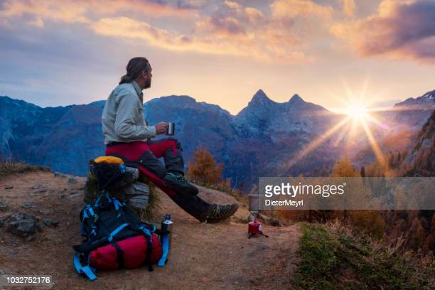 climber enjoys coffee at sunrise in alps - upper bavaria stock photos and pictures