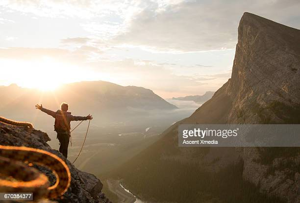 Climber enjoys sunrise over distant peaks, rope
