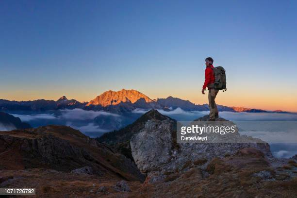 climber enjoys the sunrise with a view to the summit watzmann at alpenglow - alps - berchtesgaden stock pictures, royalty-free photos & images
